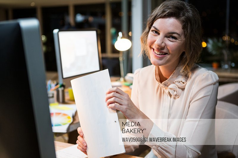 Portrait of businesswoman holding document at her desk in the office