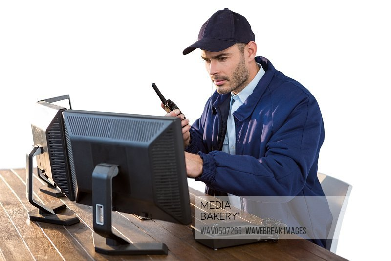 Security officer looking at computer monitors and talking on walkie-talkie against white background