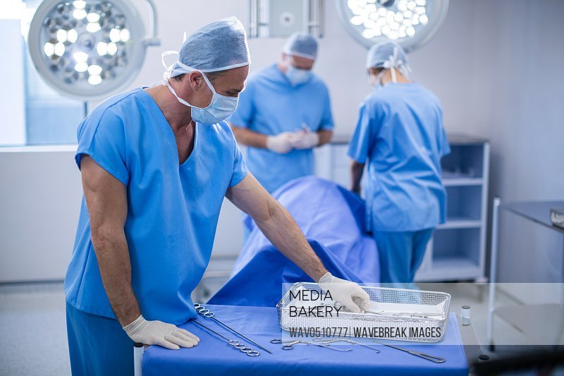 Surgeon removing surgical tools from tray in operation room at the hospital