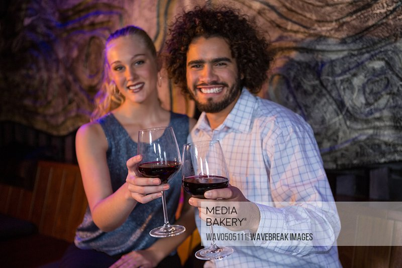 Portrait of smiling couple holding a glass of wine in bar
