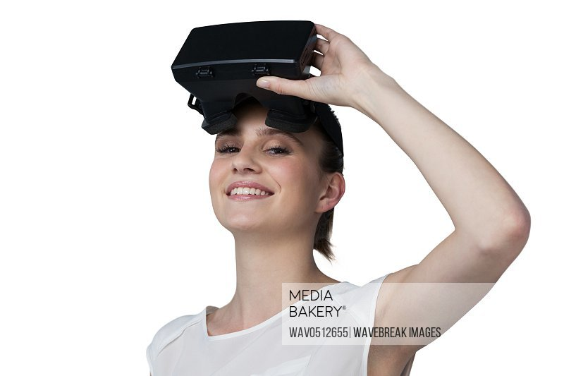 Portrait of beautiful woman holding virtual reality headset against white background