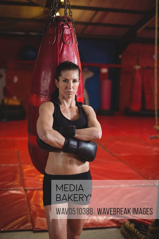 Portrait of female boxer standing with arms crossed in fitness studio