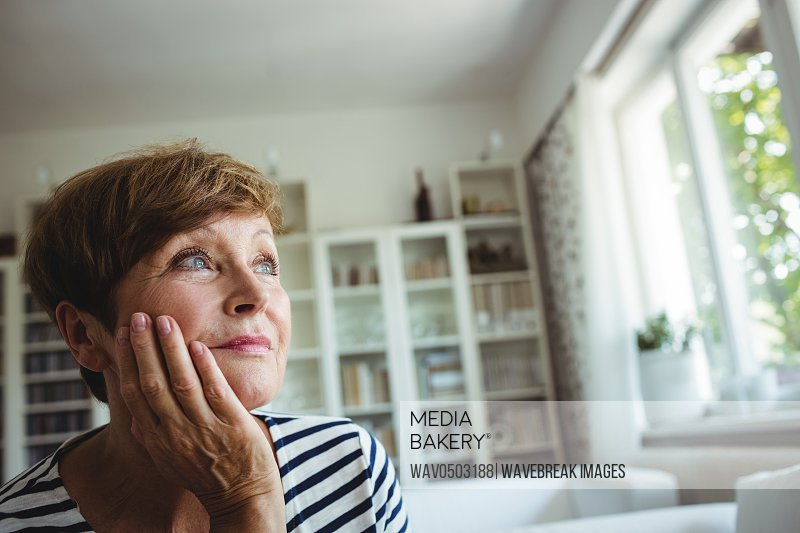 Thoughtful senior woman sitting on sofa in living room at home