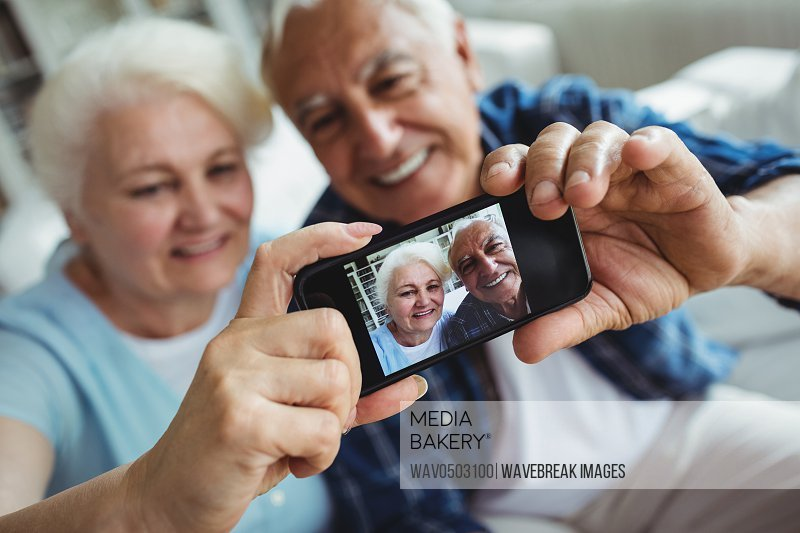 Senior couple taking a photo from mobile phone at home