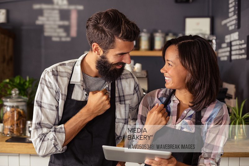 Smiling waiter and waitress interacting while using digital tablet in cafA?