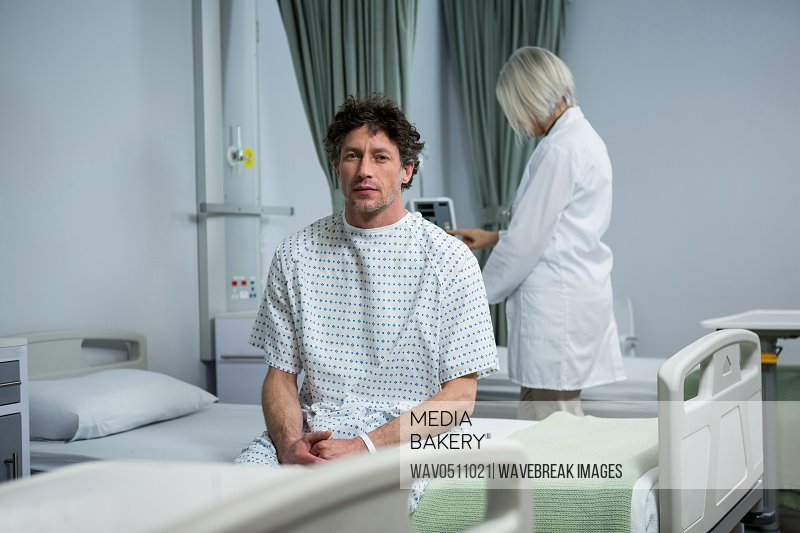 Portrait of patient sitting on bed in ward while doctor standing in background