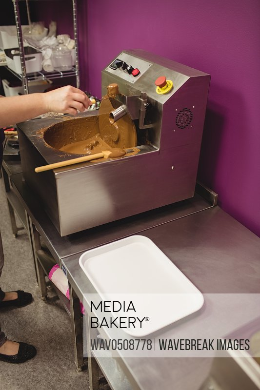 Worker dipping marshmallow in chocolate blending machine