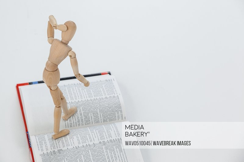 Wooden figurine standing on an open book against white background