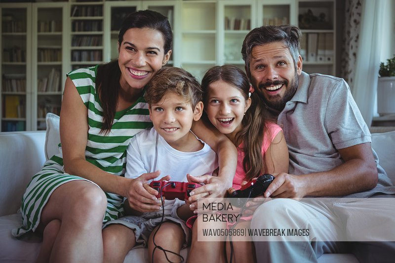 Parents sitting on sofa with their children and playing video games at home
