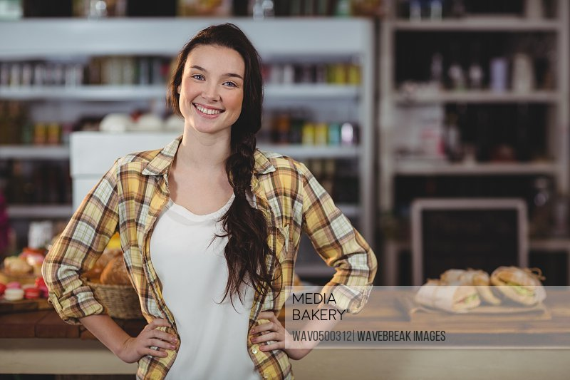 Portrait of woman standing behind the counter in cafe