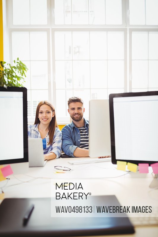 Portrait of cheerful graphic designers sitting at desk in creative office