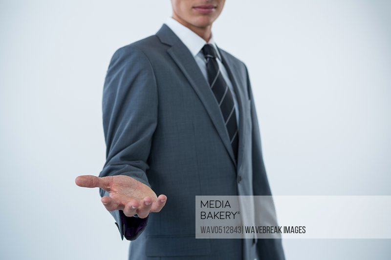 Mid section of a businessman offering a helping hand against white background
