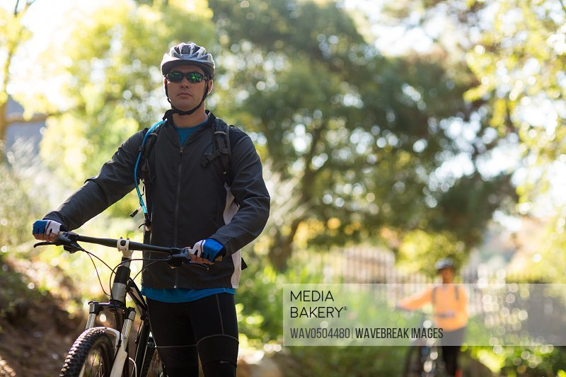 Male biker standing with mountain bike in countryside
