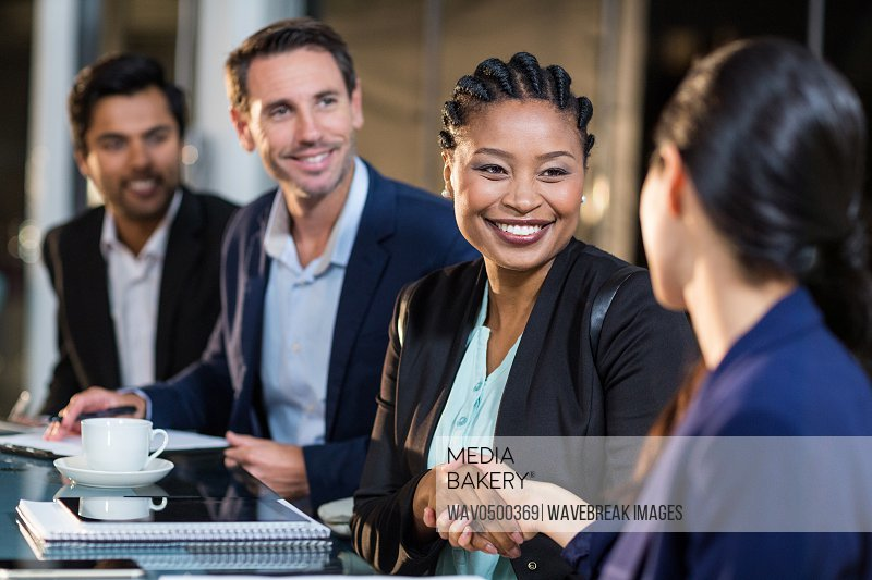 Businesswoman shaking hands with colleague in the office