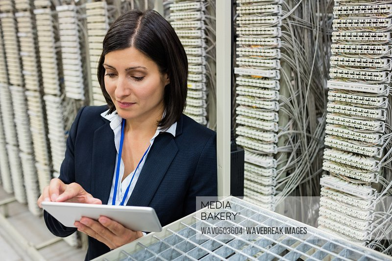Attentive technician using digital tablet in server room