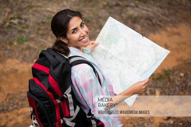 Portrait of smiling female hiker holding map in forest