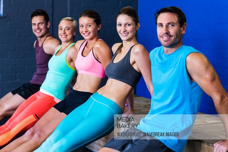 Portrait of happy athletes exercising on wooden box in gym