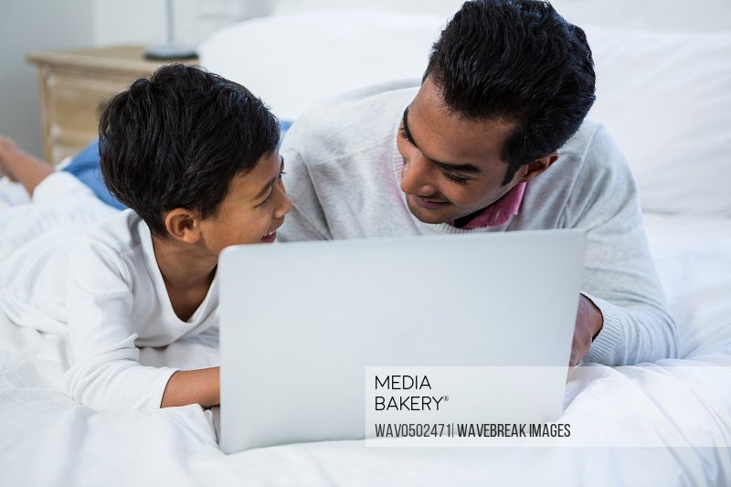Father and son using laptop on bed in the bedroom