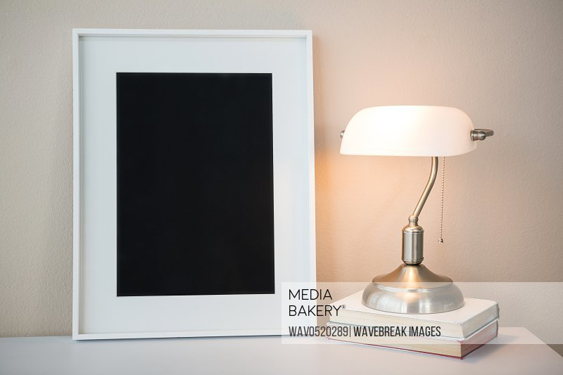 Picture frame with books and table lamp