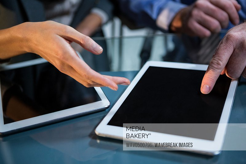 Close-up of businessman discussing with colleague over digital tablet in the office