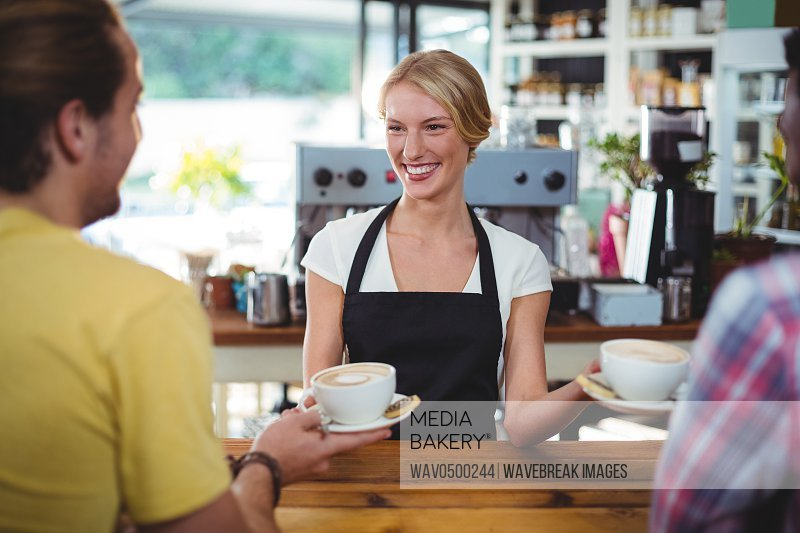 Smiling waitress serving cup of coffee to customer in cafe