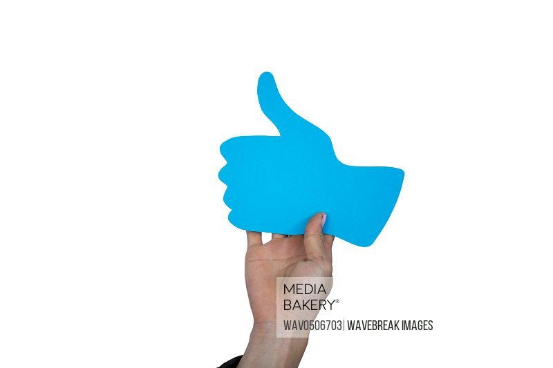 Hand of man holding thumbs up sign board against white background