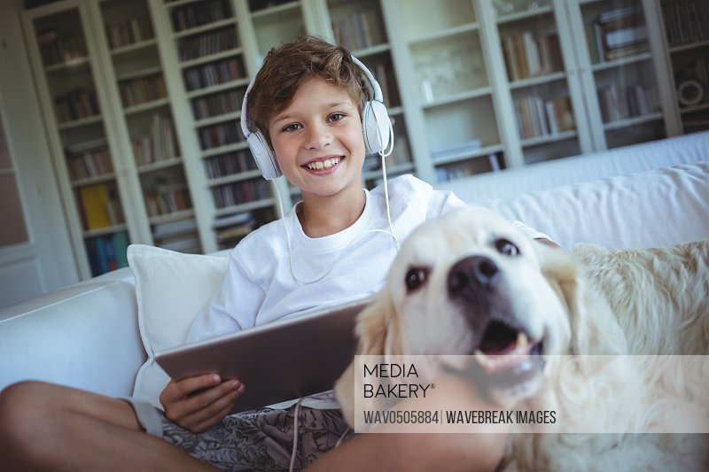 Boy sitting on sofa with pet dog and listening to music on digital tablet at home