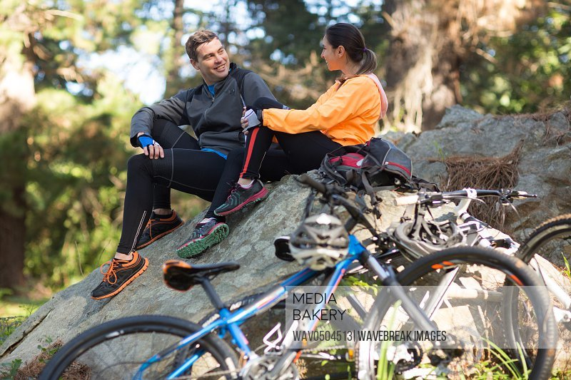 Biker couple interacting with each other in forest at countryside