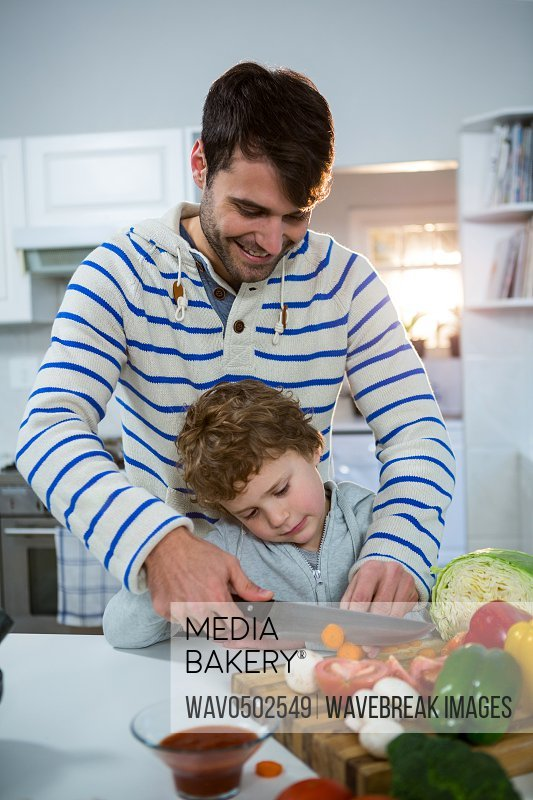 Father teaching his son how to chop vegetables in the kitchen at home
