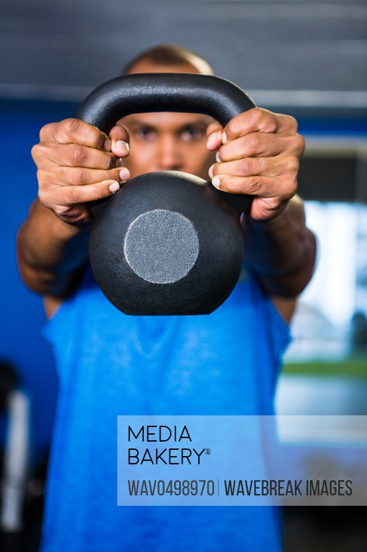Man covering face with kettlebell while exercising in gym