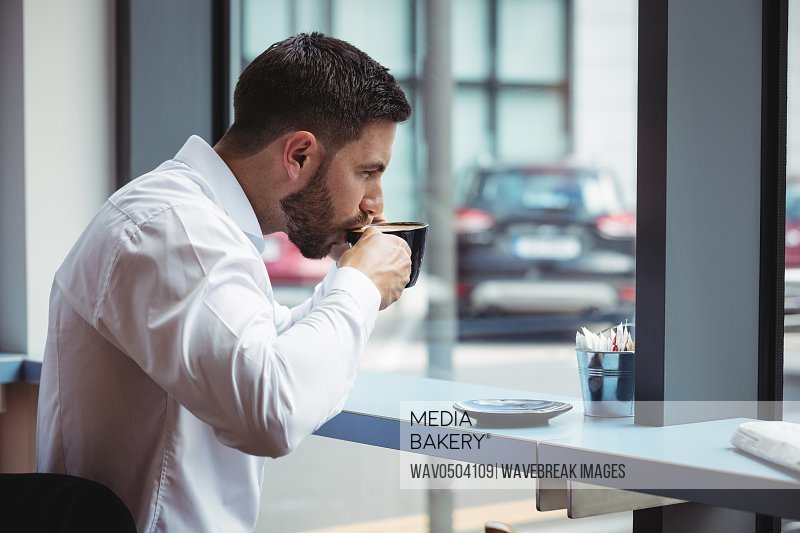 Businessman having a cup of coffee in office