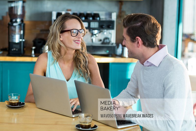 Man and woman interacting while using laptop during meeting in cafe