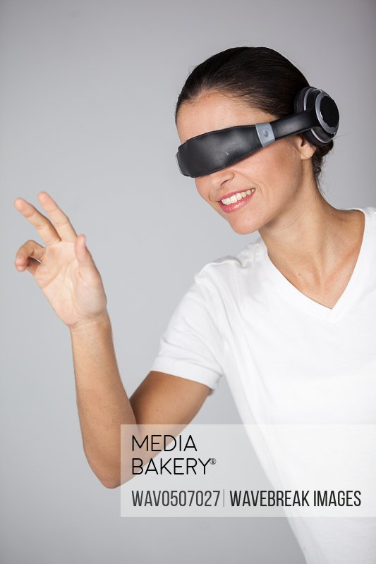 Woman using virtual video glasses against white background