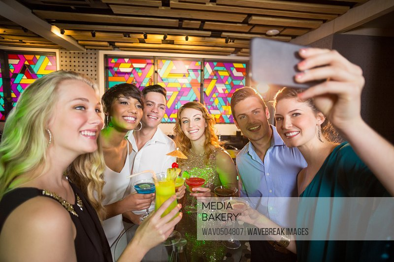 Group of friends taking selfie from mobile phone while having cocktail in bar