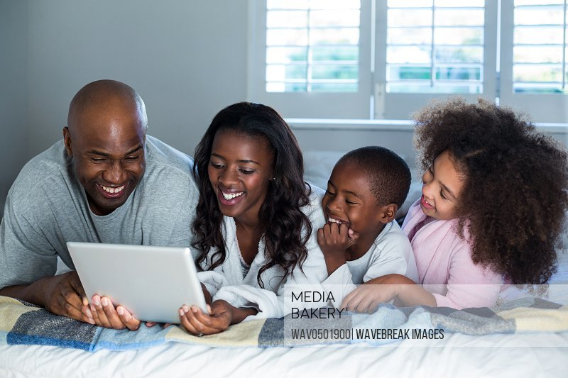 Family using digital tablet on bed at home