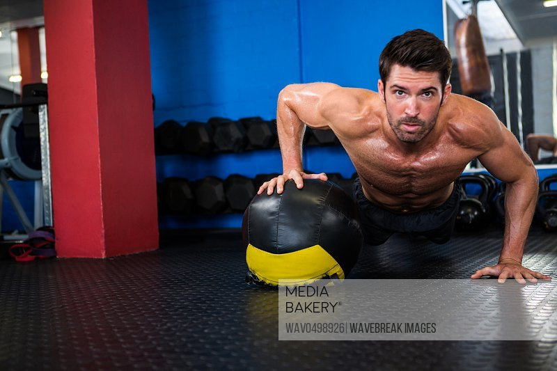 Portrait of young shirtless athlete doing push-ups with exercise ball at gym