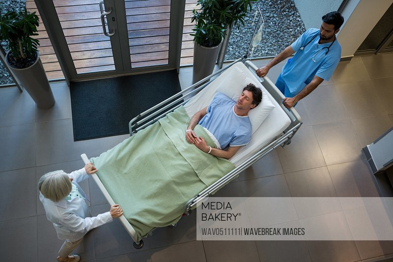 Doctors pushing emergency stretcher bed in corridor at hospital
