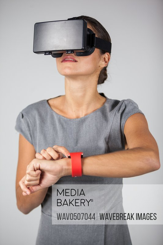 Woman touching smart watch and using virtual reality headset against white background