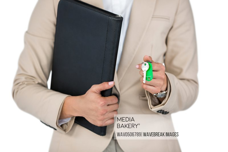 Mid-section of Businesswoman holding a file and key against white background
