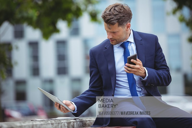 Handsome businessman holding mobile phone while using digital tablet outside office