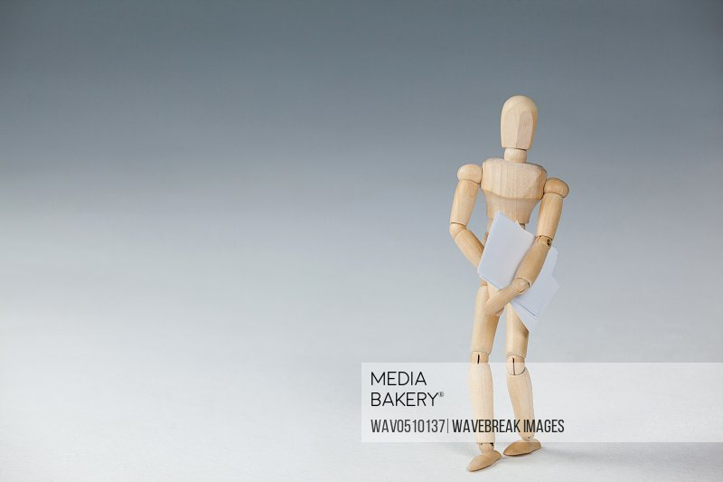 Wooden figurine standing and holding documents against white background