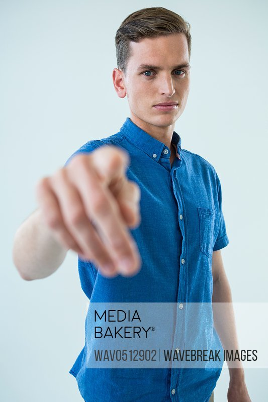 Portrait of man touching an invisible screen against white background