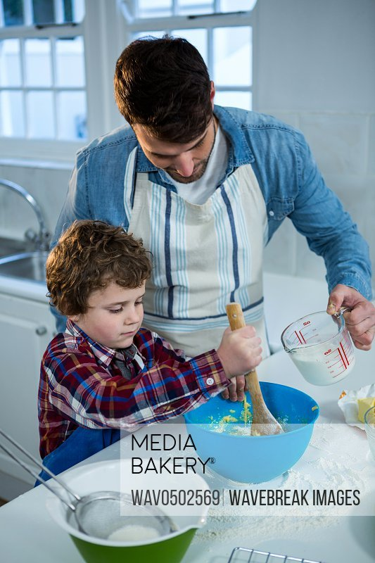 Father and son preparing cupcake in the kitchen