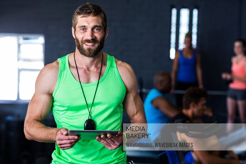 Portrait of happy hipster holding tablet while standing in gym
