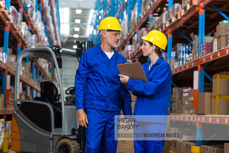 Warehouse workers discussing with clipboard in warehouse