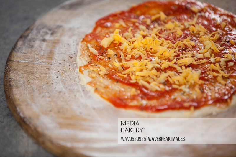 Pizza dough with tomato sauce with grated cheese