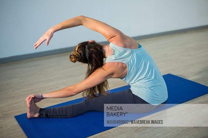 Woman performing head of the knee pose on exercise mat in fitness studio