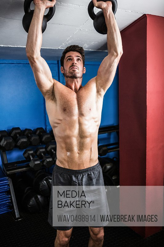Shirtless athlete lifting kettlebells while standing in gym