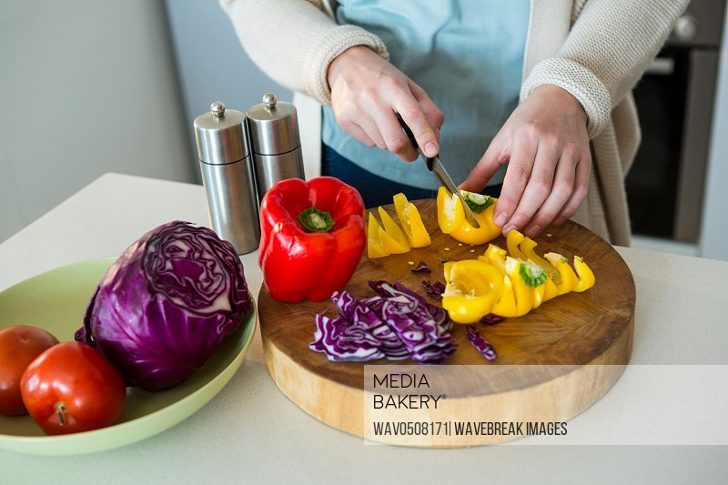Mid section of woman cutting yellow bell pepper in kitchen at home