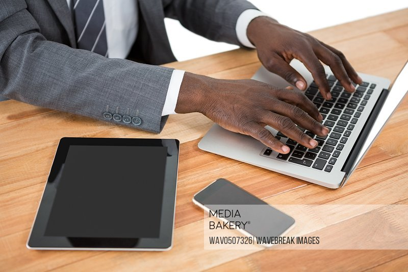 Mid section of businessman using laptop and other multimedia devices at desk
